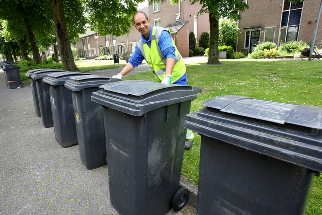 Garbage man picks up waste containers